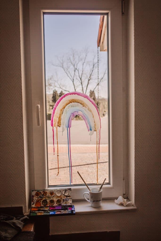 regenbogen gegen corona. kinder malen regenbogen an die Fenster