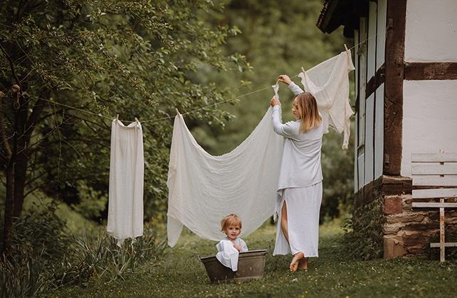 mama mit kind hängt wäsche auf