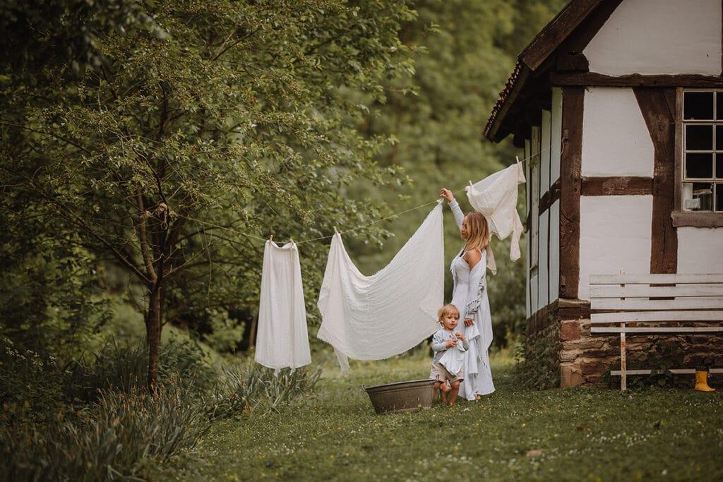 Familienfotografie Mutter hängt wäsche auf und Kind hilft mit
